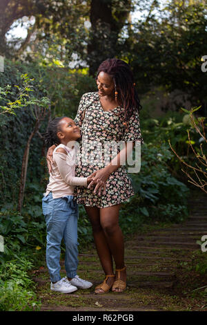 Mother and daughter looking at each other lovingly on a garden path - Stock Image