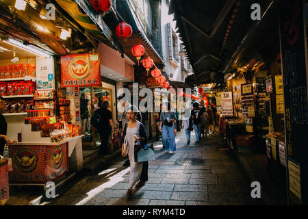 Jiufen, Taiwan - November 07, 2018: A young woman walks with purchases at the Old Street market on November 7, 2018, in Jiufen, Taiwan - Stock Image