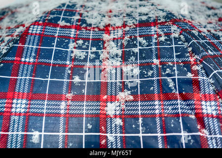 snowflakes over a blue and red colored umbrella - Stock Image