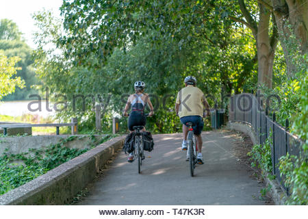 Couple cycling along the thames near Richmond, England - Stock Image