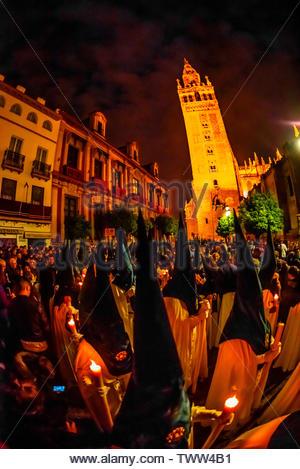 Hooded Penitents (Nazarenos) in the procession of the Brotherhood (Hermandad) La Macarena, early morning on Good Friday, Holy Week (Semana Santa), Sev - Stock Image