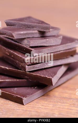 Broken chocolate pieces on dark background - Stock Image