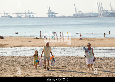 Holidaymakers enjoy the Summer sun on the beach at Plage de Butin, Honfleur, France with the gantry cranes of container port of Le Havre across the Se - Stock Image