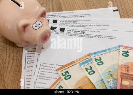 Paris, France - November 15, 2018 : The various French taxes return, piggy bank and banknotes in euros - Stock Image