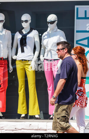 Miami Beach Florida Collins Avenue man woman couple walking storefront store window shopping clothing fashion mannequins color - Stock Image
