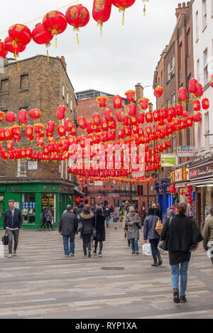 Tourists walk around the streets of Chinatown, London, UK - Stock Image