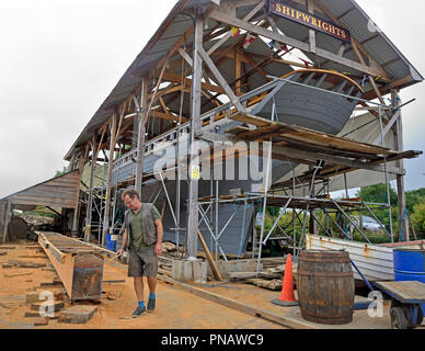 Luke Powell and his apprentice shipwrights working on his project and the build of the 68 ft Falmouth Pilot Cutter 'Pellew'at The Rhoda Mary Ship yard - Stock Image