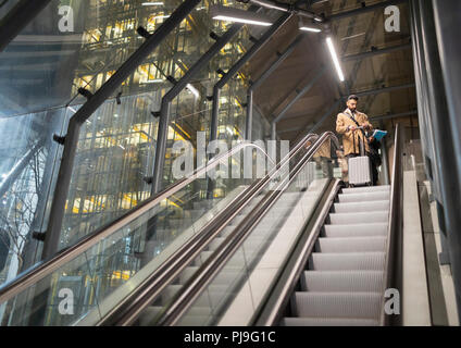 Businessman with suitcase on urban escalator - Stock Image