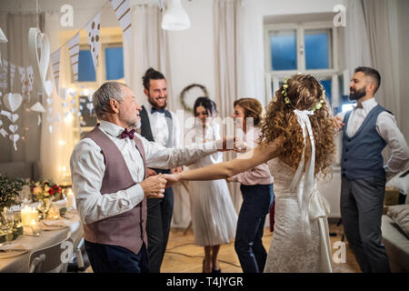 A young bride dancing with father or grandfather and other guests on a wedding reception. - Stock Image