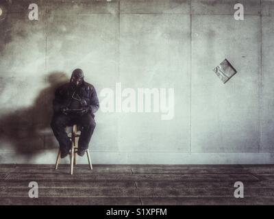 Man sat on a stool in New York City reading his tablet. - Stock Image