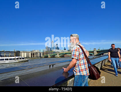 London, England, UK. Bearded man looking out over the River Thames from the South Bank. City of London skyline behind - Stock Image