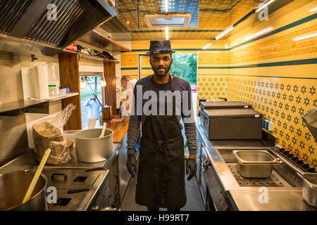 Man with hat and apron in commercial kitchen of food truck - Stock Image