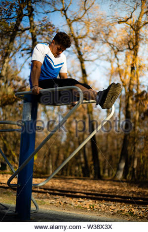 Man doing abs workout on parallel bars outdoors on fall during sunset - Stock Image
