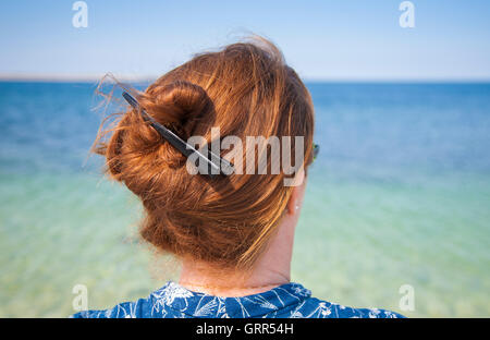 Woman with long hair wearing her hair in a knot gazing out over the sea - Stock Image