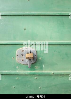 Brass padlock securing lock-up unit - Stock Image