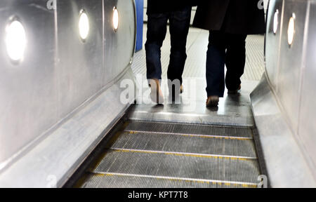 Two men using the London underground escalators with intentional blurred motion and movement - Stock Image