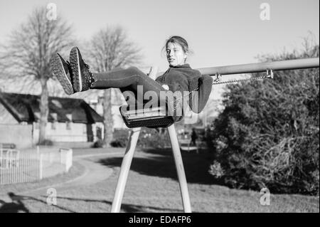 Girl on a swing in a playground in Daventry, Northamptonshire during the winter - Stock Image