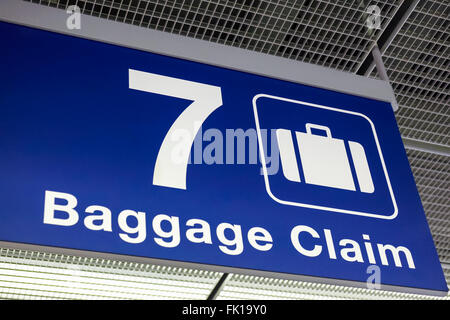 A blue airport baggage claim sign hanging from the ceiling - Stock Image