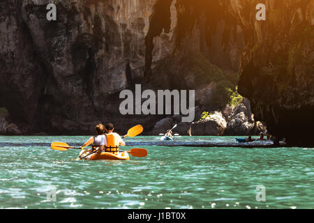 Travel concept with kayakers on sea bay backdrop - Stock Image