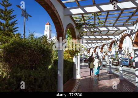 Chefchaouen, Morocco : Two women walk at Mohamed V square outside the medina. Former Spanish church in background. - Stock Image
