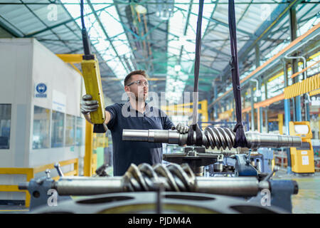 Engineer moving partly finished gear parts in gearbox factory - Stock Image