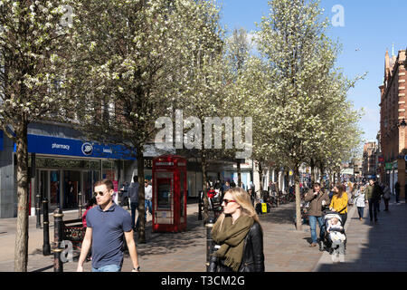 Shoppers and visitors to Worcester High Street with spring blossom on the trees - Stock Image