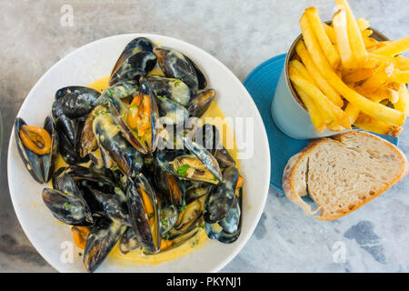 Moules Mariniere served with thin Chips and Sourdough bread lunchtime meal at the Seaview Café Saltburn North Yorkshire UK - Stock Image
