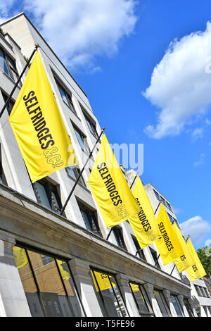 Selfridges department store using yellow banner to advertise the brand image & repeat on long row of identical banners for impact London West End UK - Stock Image