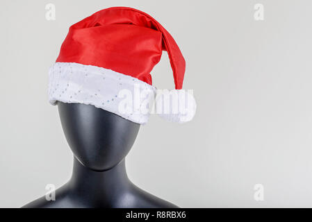 A head of female mannequin with santa claus hat isolated on white background - Stock Image