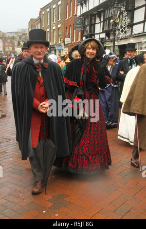 Rochester, Kent, UK. 1st December 2018: A couple dressed in Victorian costume particiapte in the Main parade on Rochester High Street. Hundreds of people attended the Dickensian Festival in Rochester on 1 December 2018. The festival's main parade has participants in Victorian period costume from the Dickensian age. The town and area was the setting of many of Charles Dickens novels and is the setting to two annual festivals in his honor. Photos: David Mbiyu/ Alamy Live News - Stock Image