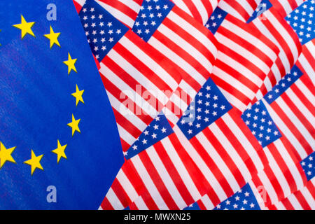 Stars and Stripes flags & EU flag - metaphor for Trump Trade Tariffs on EU imports to USA, Trump steel tariffs, also general concept of trade barriers - Stock Image