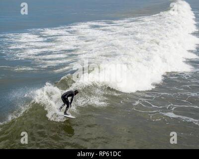 Surfer enjoying a good wave at Saltburn North Yorkshire February 2019 - Stock Image
