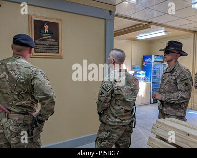 "British Army Brigadier Simon Humphrey (left), commander of the Kabul Security Force (KSF), and Oklahoma Army National Guard (OKARNG) members (right) of 1st Squadron, 180th Cavalry Regiment, 45th Infantry Brigade Combat Team, observe a recently unveiled plaque after a dedication ceremony at the newly remodeled New Kabul Compound (NKC) flight terminal on Friday, Aug. 31, 2018 in Kabul, Afghanistan. The ""Hughie Terminal"" at NKC is named after the late Poteau, Oklahoma resident, Sgt. Buddy James ""Doc"" Hughie, member of Charlie Company, 1st Battalion, 180th Infantry Regiment, who was killed in acti - Stock Image"