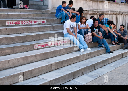 People sitting on the entry steps to the Blue Mosque, Sultanahmet, Istanbul, Turkey - Stock Image