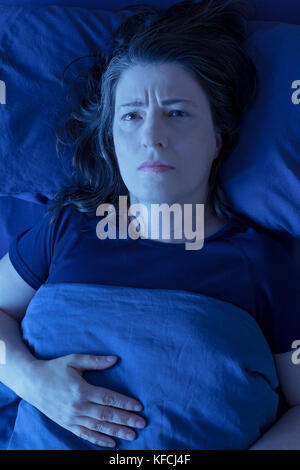 Middle aged woman lying awake in her bed at night because of insomnia, stress, fears, nightmares or restless leg - Stock Image