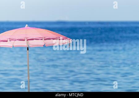 Pink beach umbrella against mediterranean sea - Stock Image