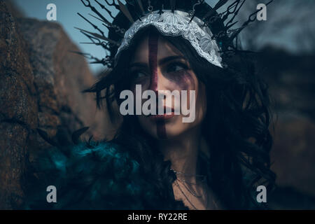 Portrait of young woman in the image of a fairy and a sorceress in a black dress and a crown. - Stock Image
