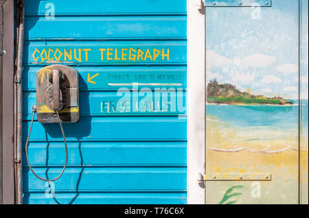 Coconut telegraph, an old phone mounted on an exterior wall in St Barts, explaining that it is a way to communicate directly with Key West - Stock Image