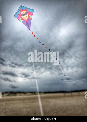 Holiday kite flying on a beach in the UK - Stock Image