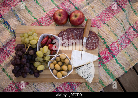 Fruits and salami on picnic blanket - Stock Image