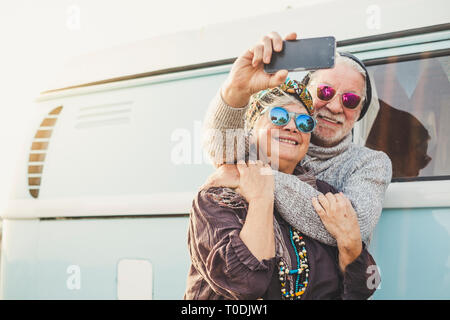 70 years old cheerful happy adult couple take a selfie picture outside a intage blue van with modern technologyh - tourism and tourist concept for peo - Stock Image