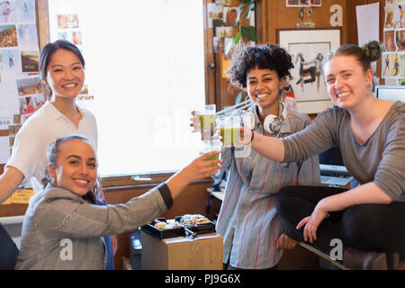 Portrait confident creative female designers drinking green smoothies in office - Stock Image