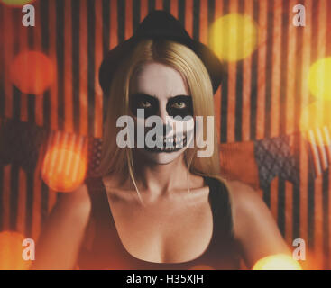 A woman is wearing skeleton makeup on her face with orange party lights for a halloween celebration or costume idea. - Stock Image