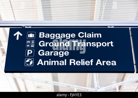 Airport baggage claim sign with Ground Transport, Garage, and Animal Relief Area. - Stock Image