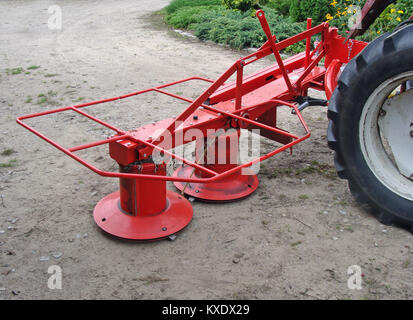 Red color tractor powered rotary mower with two rotors - Stock Image