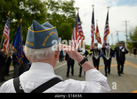 Merrick, New York, U.S. - May 26, 2014 - A veteran salutes fire fighters marching in The Merrick Memorial Day Parade and Ceremony, hosted by American Legion Post 1282 of Merrick, honors those who died in war while serving in the United States military. © Ann E Parry/Alamy Live News Credit:  Ann E Parry/Alamy Live News - Stock Image
