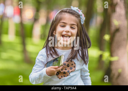 Adorable four years old cute little girl in casual clothes holds mobile phone while laughing at outdoor in park - Stock Image
