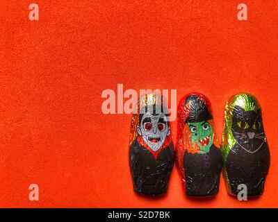 Three Halloween themed foil wrapped chocolates on a plain bright orange background with copy space - Stock Image