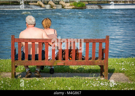 An older couple enjoying the afternoon sun sitting on a bench on the bank of the River Thames watching the world - Stock Image