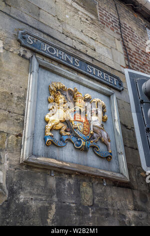 Wooden wall plaque with coat of arms by the St John's Street entrance to Cathedral Close, Salisbury, a cathedral city in Wiltshire, south-west England - Stock Image